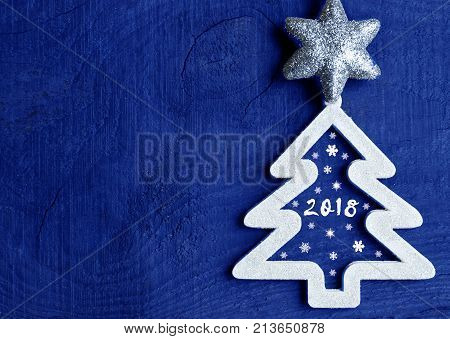 White christmas tree with 2018 number on dark blue wooden background.Happy new year 2018 concept.