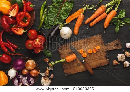 Cooking ingredients background. Sliced carrots and vintage knife on cutting board, vegetables, herbs and spices on kitchen table. Vegetarian cuisine and food preparation concept, top view