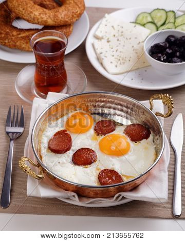 Turkish breakfast with fried egg, roasted sucuk, cheese, vegetables, simits, and Turkish tea