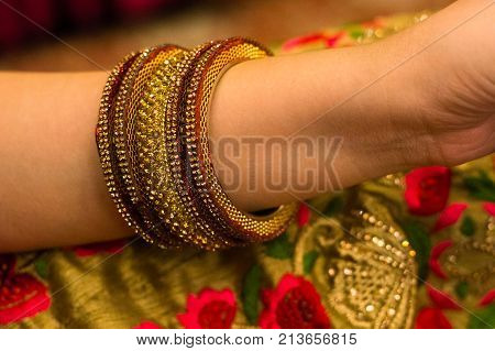 Beautiful gold and red bangles on the arm of an indian lady wearing a flower dress. These are central ornaments worn during and occassion by hindu ladies