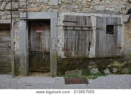 A disused building in hill village of Erto in Friuli Venezia Giulia north east Italy. The village is famous locally for having being evacuated following the 1963 Vajont Dam disaster. The sign on the door indicates that the building is for sale