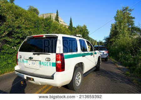 GLACIER NATIONAL PARK, MONTANA, USA - July 22, 2017: United States Park Ranger SUV pulls into traffic on Going to the Sun Road in Glacier National Park. Traffic was stopped due to a bear sighting.