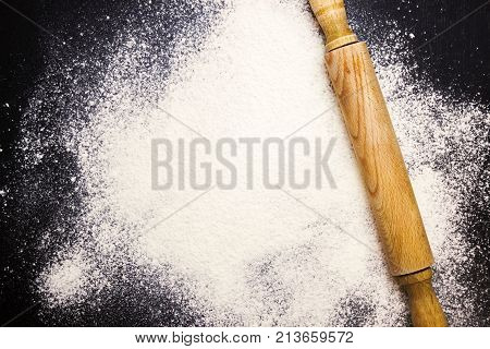 An overhead photo of rolling pin and wheat white flour sprinkled on the black wooden table. Top view place for text. Flour ready to knead the dough for baking bread cake or cupcake