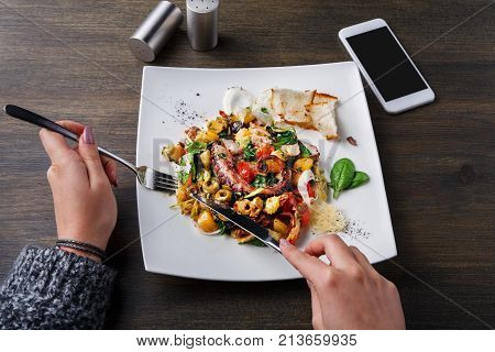 Eating salad with octopus and vegetables pov. Unrecognizable person dining on appetizing fresh mediterranean seafood meal with toasts in restaurant