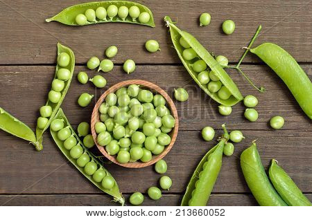 Fresh green peas in wooden bowl pods of green peas top view