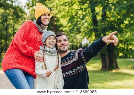 Enjoying good atmosphere. Family harmony. Happy family walk in green park, have happy expressions. Affectionate father points with fore finger into distance as tries to show beautiful sunset