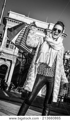Rediscovering things everybody love in Milan. Full length portrait of smiling modern woman in fur coat and sunglasses at Piazza del Duomo in Milan Italy rejoicing