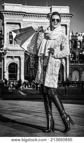 Rediscovering things everybody love in Milan. Full length portrait of smiling young woman with shopping bags near Galleria Vittorio Emanuele II in Milan Italy looking into the distance