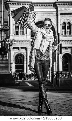 Rediscovering things everybody love in Milan. Full length portrait of happy elegant woman with shopping bags at Piazza del Duomo in Milan Italy rejoicing