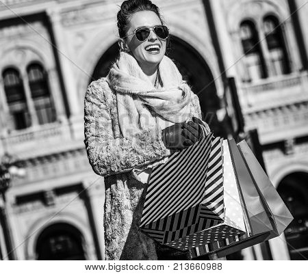 Rediscovering things everybody love in Milan. smiling young traveller woman with shopping bags near Galleria Vittorio Emanuele II in Milan Italy looking into the distance