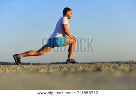 Man With Sportive Figure Does Stretching. Trainer Does Warmup Exercises