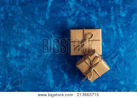 gift a surprise in the box is packed in brown vintage paper and tied with a rope scoop. Christmas concept. on a blue homogeneous background