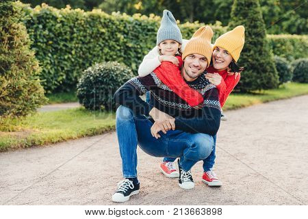 Beautiful female, little girl embrace their handsome father and husband, have good relationship, have active lifestyle, pose against green trees. Family have walk together, embrace each other