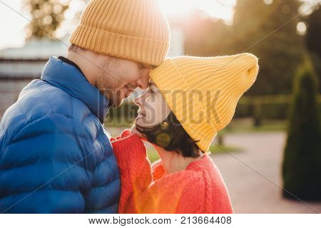 Romantic young couple look at each other with great love, have nice relationship, going to kiss, have walk outdoor in park, wear warm clothes. Lovely couple with eyes full of love and smile.