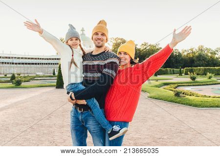 Three people have good time together: mother, father and small daughter stand next to each other, walk outoors, wave with hands, have happy expressions. People, facial expressions and emotions