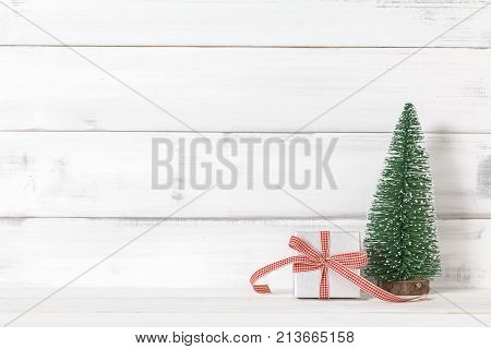Gift box with christmas tree on white wood over white rustic background with copy space for text