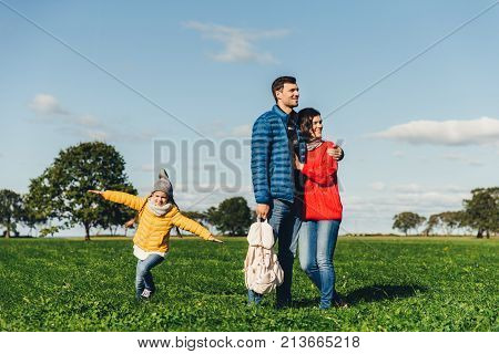 Young couple in love stand on green grass, embrace and look pensively. Playful small child enjoys freedom, runs on field, plays near her parents, has good mood and recreation. Peope and nature