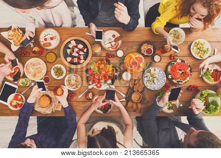 Gadget device addiction, friends dinner with smarphones, online in social networks while eating food together, wooden table top view.