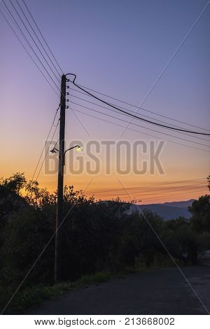 Vintage Telegraph Post With Illuminating Street Lantern At Sunset. Corfu, Greece.