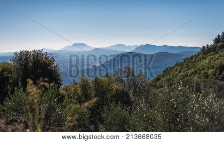 View Over Mountains In Hazy Sunlight. Corfu, Greece.