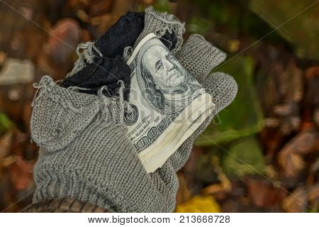 homeless man holds money in a torn woolen glove