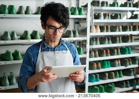 Modern shoe master with tablet taking online orders from clients