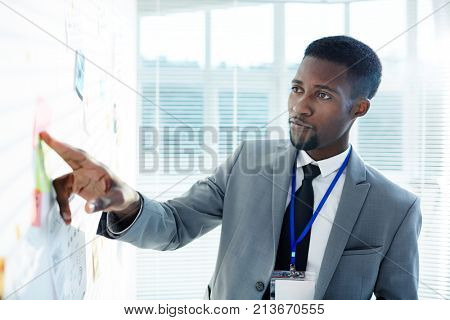 Young inspector in suit pointing at evidence on whiteboard