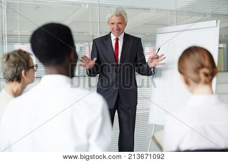 Successful coach or boss standing by whiteboard and making presentation of new details of crime to his subordinates