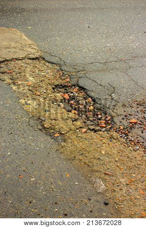 Waterfilled pothole on asphalted road. pothole on asphalt