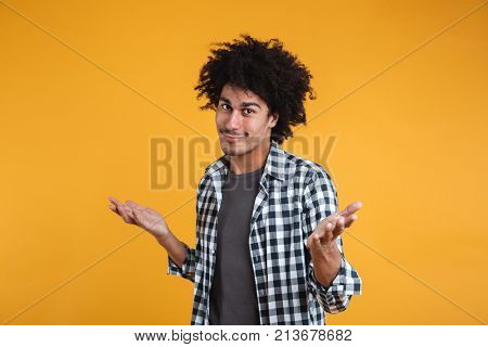 Portrait of an unconfident young afro american man shrugging shoulders and looking at camera isolated over orange background