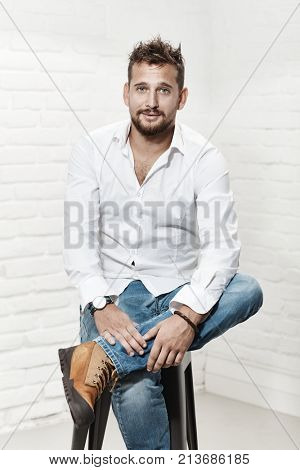 Portrait of handsome casual guy sitting on barstool indoor smiling.