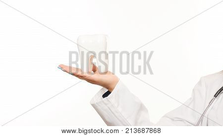 Female doctor hand holding white healthy human tooth model isolated on white background. Oral dental hygiene. Teeth Whitening. Dental health Concept. Oral Care, teeth restoration.