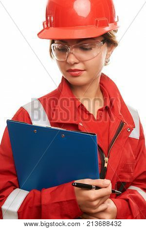 Young woman engineer and technician wearing safety hard hat, uniform and glasses are checking the list on the clipboard isolated on white background, close-up portrait