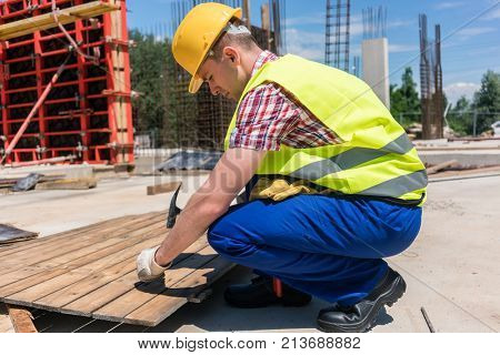 Side view of a young worker wearing safety vest and yellow hard hat while hammering a nail into wood, during work on the construction site of a contemporary building