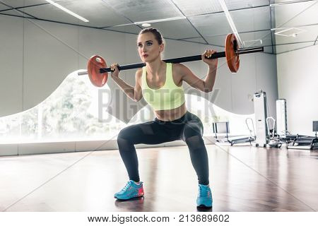 Full length low-angle view of a beautiful determined young woman holding a barbell behind the neck, for shoulder muscles during functional training workout at the gym