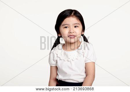 Studio portrait of Asian girl looking happy in front view