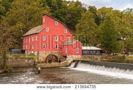 The historic Red Mill in Clinton NJ with people fishing in the river. The village also decorated for halloween as photo taken in Mid October