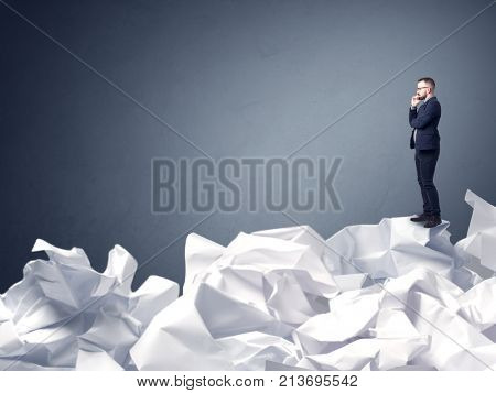 Thoughtful young businessman standing on a pile of crumpled paper with a blueish grey background