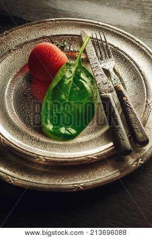 Fresh wet spinach leaf and tomato on a shinny silver plate