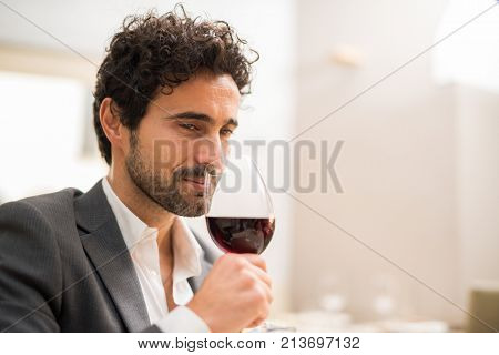 Man smelling a glass of red wine