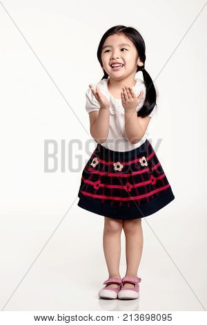 Studio portrait of Asian girl trying to cover face with hands