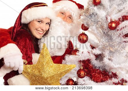 mr and mrs santa claus decorating the christmas tree