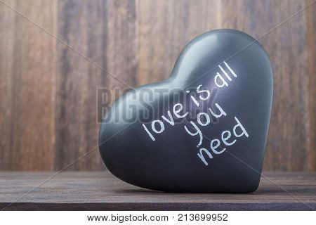 ceramic black heart on wooden background with message as valentines day symbol