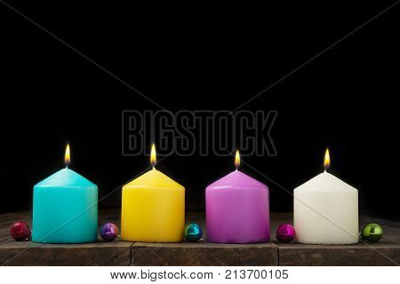 Multicolored burning candles with decorative small balls on black background.Concept of New Year and Xmas