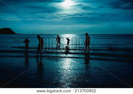 Landscape of green sky with bright full moon over seascape and silhouette of six person standing in the sea. Family enjoying and relaxing on beach. Serenity nature background. The moon taken with my camera.