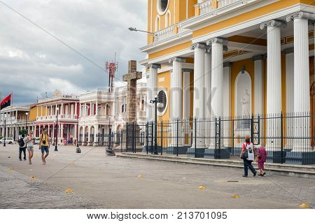 Granada Nicaragua - July 22 2015: Tourists and local people walk past the Cathedral of Our Lady of the Assumption in Granada Nicaragua. Its Spanish name is Catedral de Nuestra Senora de la Asuncion