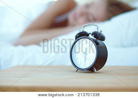 Young sleeping woman and alarm clock in bedroom at home. Young sleeping woman.