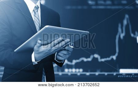Businessman using digital tablet, raising graph background. Business growth, investment and invest in stock exchange market