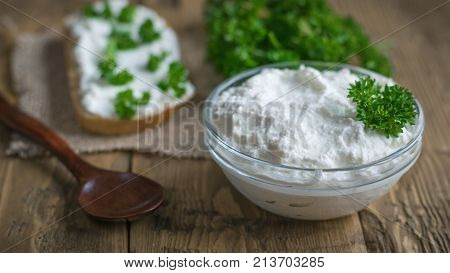 A fresh slice of bread smeared with cottage cheese cream with parsley on the table. The concept of a healthy diet. Curd cream.