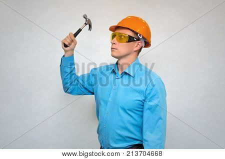 Builder worker in hardhat looking forward and holding hummer in hands isolated. Construction people. Man hammers a nail.